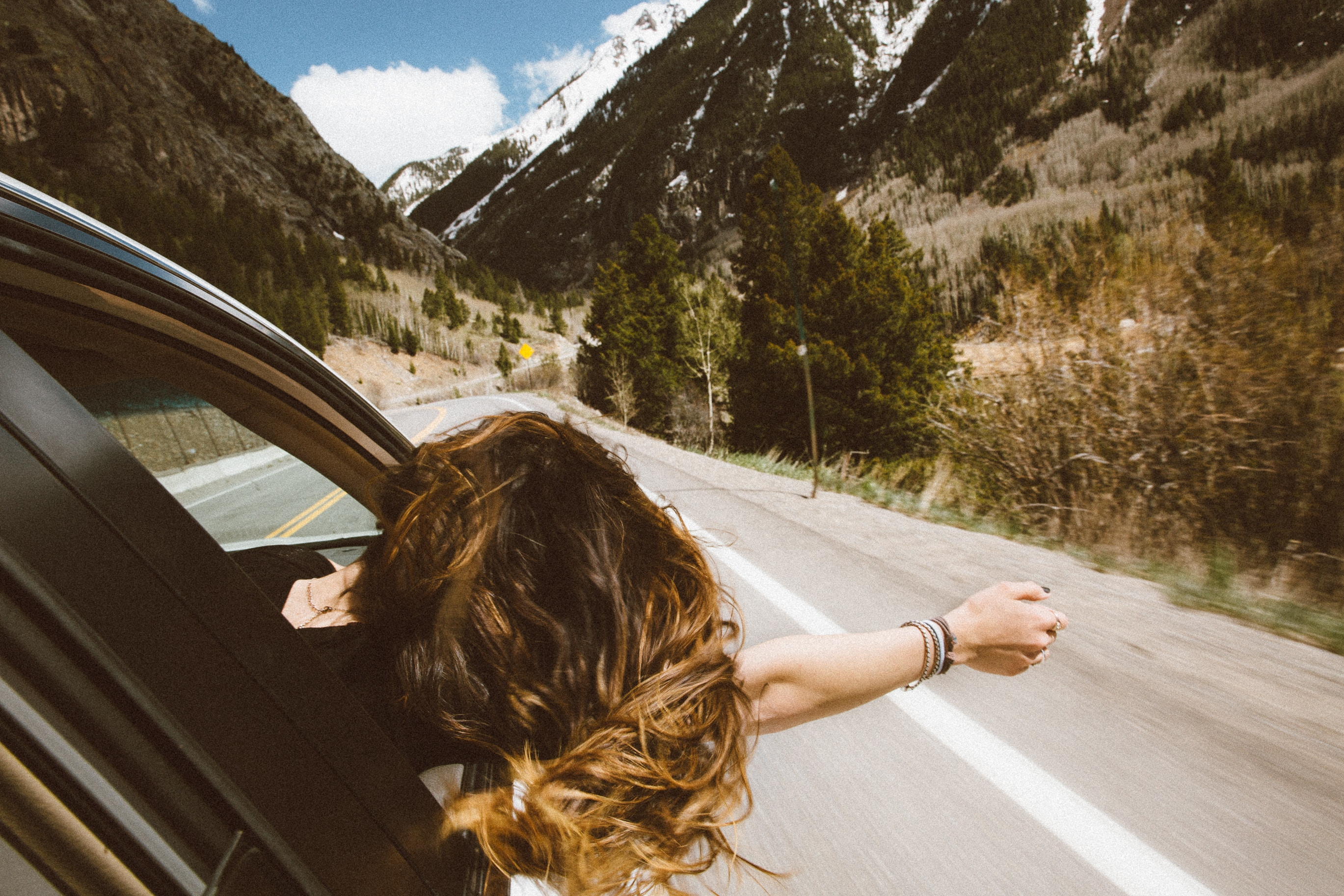 woman in car on her journey toward mountains - might need faith